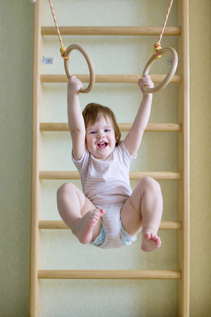 boy gymnast: Baby doing exercises on the gymnastic rings. Healthy lifestyle since childhood concept. Stock Photo