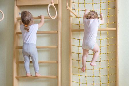 niño trepando: Dos bebés de los niños que suben por las escaleras de gimnasia. Foto de archivo