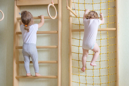 gymnastics equipment: Two baby toddlers climbing up the gymnastic stairs.