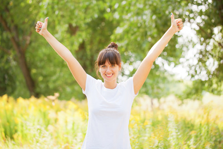 Woman in white t-shirt showing a thumbs up sign outdoors. Ready for your text or symbols.