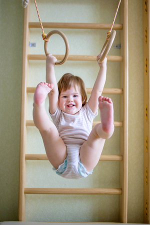 strong: Baby toddler on the gymnastic rings in the gym class. Selective focus on child`s face