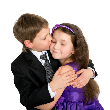 first love: Little children hugging and kissing. First love concept. Isolated on white background. Stock Photo