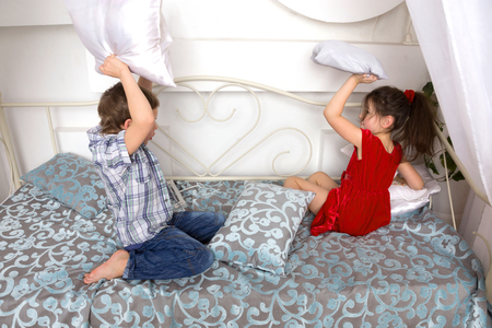 girl fighting: Little children, boy and girl fighting pillows and playing on the bed. Stock Photo