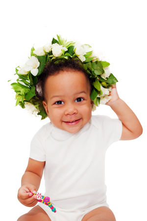 bebes niñas: bebé negro feliz en una corona de flores. Aislado en el fondo blanco Foto de archivo