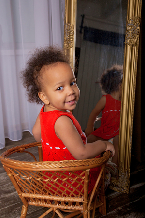looking at baby: Black mulatto baby girl sitting front of the mirror. Stock Photo