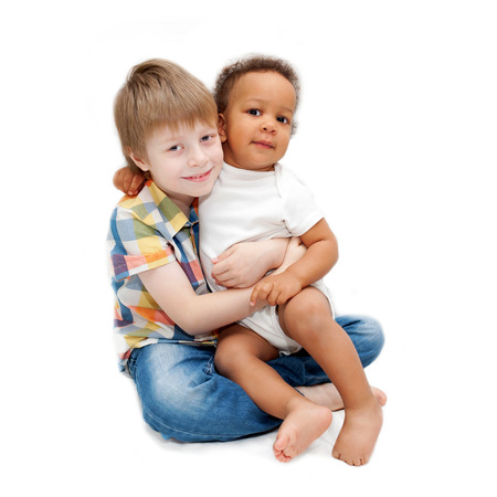 foster: Multiracial happy family. White brother hugging black baby sister.