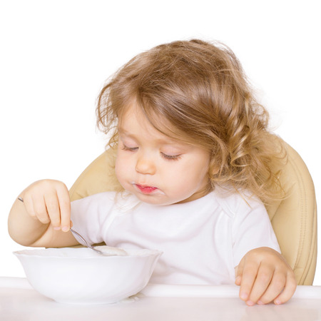 singly: Baby eating in a high chair singly. Isolated on white background. Stock Photo