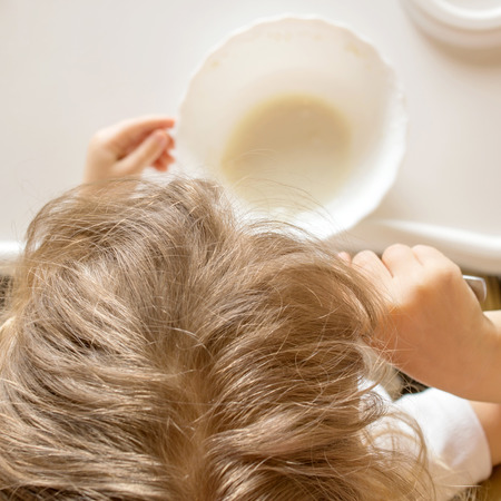 singly: Baby eating baby food in a high chair singly. Top view . Stock Photo