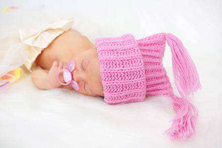 pretty baby: Pretty newborn girl sleeping. Baby dressed in a knitted cap.