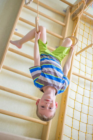 boy gymnast: Kid playing sports on the gymnastic rings in the gym class Stock Photo