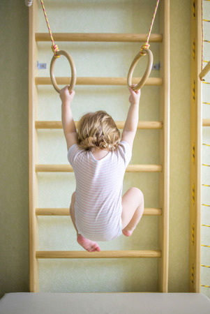 gymnastics equipment: Baby kid playing sports on the gymnastic rings in the gym class. Back view. Stock Photo