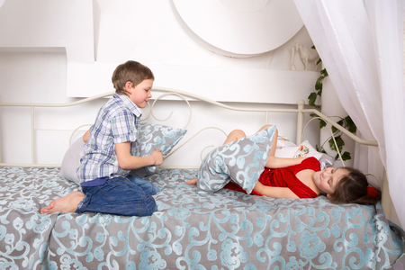 girl fighting: Little kids, boy and girl fighting pillows and playing on the bed.