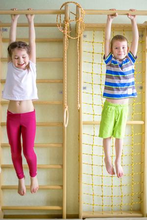 Kids playing and hanging on horizontal bar by gymnastic equipment Stockfoto