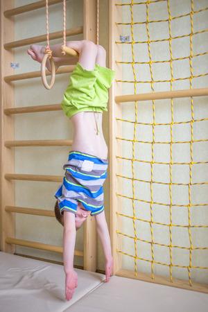 Kid haciendo deporte en el larguero de gimnasia en la clase de gimnasia Foto de archivo
