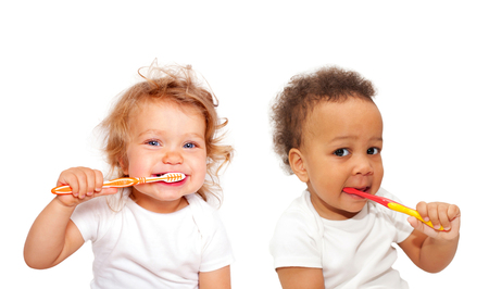 tooth cleaning: Black and white baby toddlers brushing teeth. Isolated on white background. Stock Photo