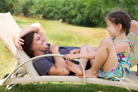 child laughing: Father and child talking on a lounger. Happy family vacation concept Stock Photo