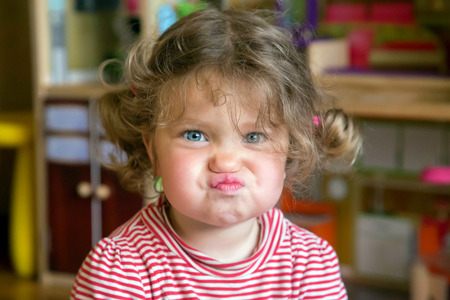 grimaces: Funny portrait of adorable baby girl. Child makes grimaces face