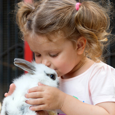 Baby girl kissing baby rabbit. Animal care concept.