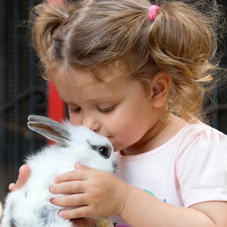 baby animal: Baby girl kissing baby rabbit. Animal care concept.