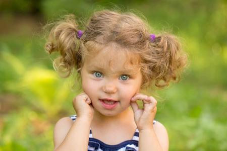 blonde yeux bleus: Cute petite fille aux cheveux blonds et yeux bleus bouclés extérieur