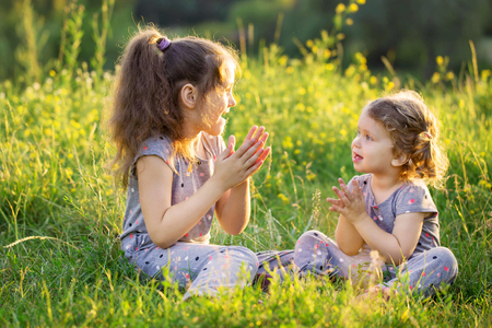 two children: Two children talking and having fun on the grass. Sisters dressed in similar clothes. Stock Photo