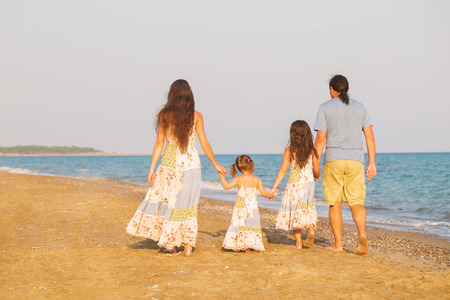 Happy family walking along the sea on the beach at sunset. Parents and children are dressed in similar clothes.