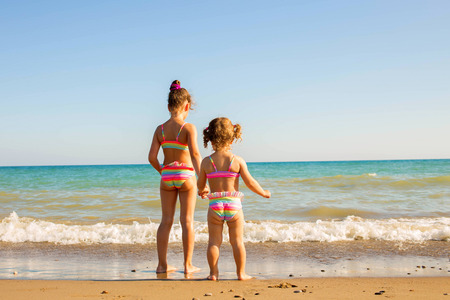 small girl: Two children looking at the the sea and holding hands. Happy family vacation concept Stock Photo