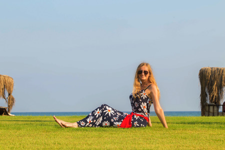 shore: Young blonde woman resting on the lawn near the sea. Summer holidays concept.