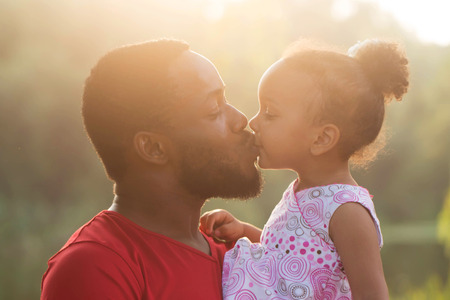 Czarny ojciec całuje córka o zachodzie słońca. Szczęśliwego koncepcji rodziny.