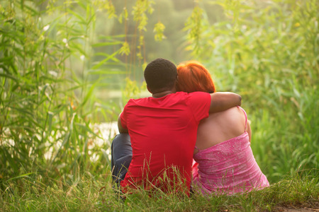 mix race: Mix race couple relaxing by the river. Black man embracing a white woman.
