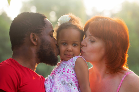 mixed family: Multiracial mixed family concept. Black father and white mother kissing baby daughter.