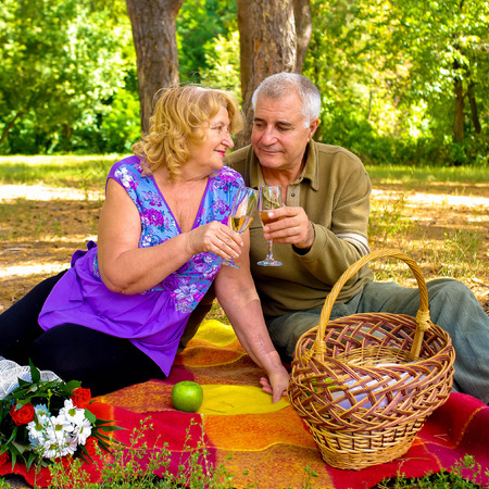 sear and yellow leaf: Family picnic. Beautiful happy old couple in love outdoors