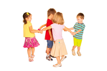 Group of little children dancing, having fun holding hands. Isolated on white background.