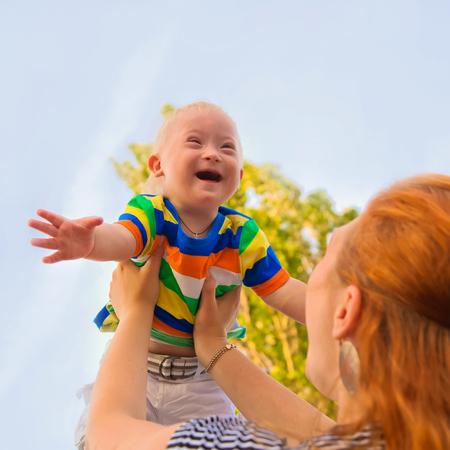 Bébé avec le syndrome de Down est heureux et voler haut Banque d'images