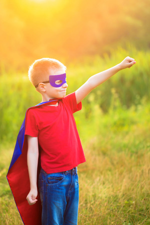 super man: Child playing and portraying super hero and super man outdoors Stock Photo