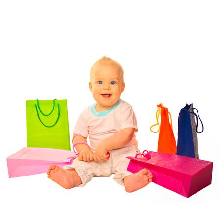 fondo para bebe: Almacenar para niños y bebés. Bebé sonriente feliz con las compras en bolsas de papel de colores. Aislado en el fondo blanco