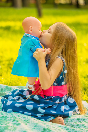 Little girl kissing her doll. Girl playing like a mother and daughter