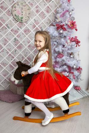 juguetes de madera: Niña en traje de Navidad en el caballo de juguete. Navidad y año nuevo concepto.