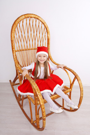 Pretty little girl wearing Christmas dress sitting on wooden rocking chair