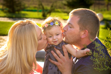 Parents kissing baby daughter. Happy family concept. Stock Photo