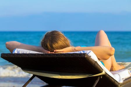 vitamina a: Joven rubia toma el sol en la tumbona en la playa cerca del mar. Concepto de vacaciones de verano.