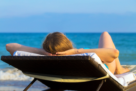 vitamina a: Young blonde woman takes sunbathing on lounger on the beach near the sea. Summer holidays concept.