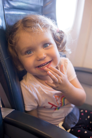 vac: Little laughing girl is traveling by plane. A small smiling child is a passenger of an airplane.