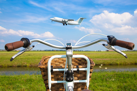 Bicycle and aircraft. Bicycle near the runway, the plane takes off. Travel background and concept.
