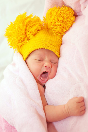 premature: The newborn baby yawns. The kid is dressed in a funny hat and covered with a blanket. Stock Photo