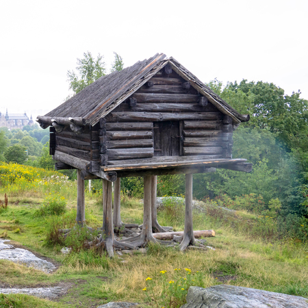 Unusual old house. Wooden house on chicken or bird legs stands on a rock. A house in which some fabulous creature lives. Stock Photo