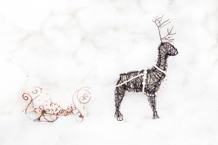 Hand made Christmas deer and Christmas sleigh against a white cotton wool background. Handmade Christmas decoration made of wire. Stock Photo