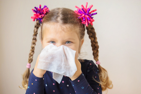 The little girl has a runny nose and blows her nose into a paper handkerchief. Childrens cold. Acute respiratory viral infection.