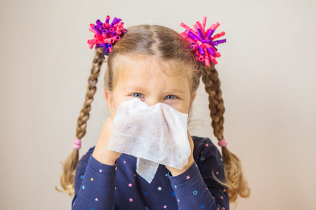 The little girl has a runny nose and blows her nose into a paper handkerchief. Childrens cold, selective focus on a handkerchief. Acute respiratory viral infection.