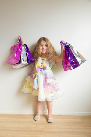 Fashion kids shopping. Beautiful smiling little girl with shopping bags and gifts. Happy child holds a lot of gifts. Sale, holidays, fashion, shopping concept.